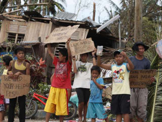group of young Filipinos holding signs asking for Typhoon Haiyan disaster relief