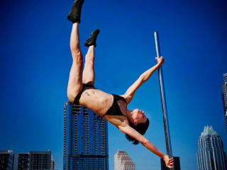 Brass Ovaries pole dancer performing in front of Downtown Austin skyline