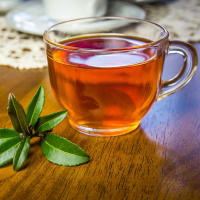 Photo of camellia sinensis leaves with cup of tea on table