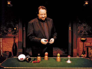 Magician Ricky Jay at table with magic and illusions stuff