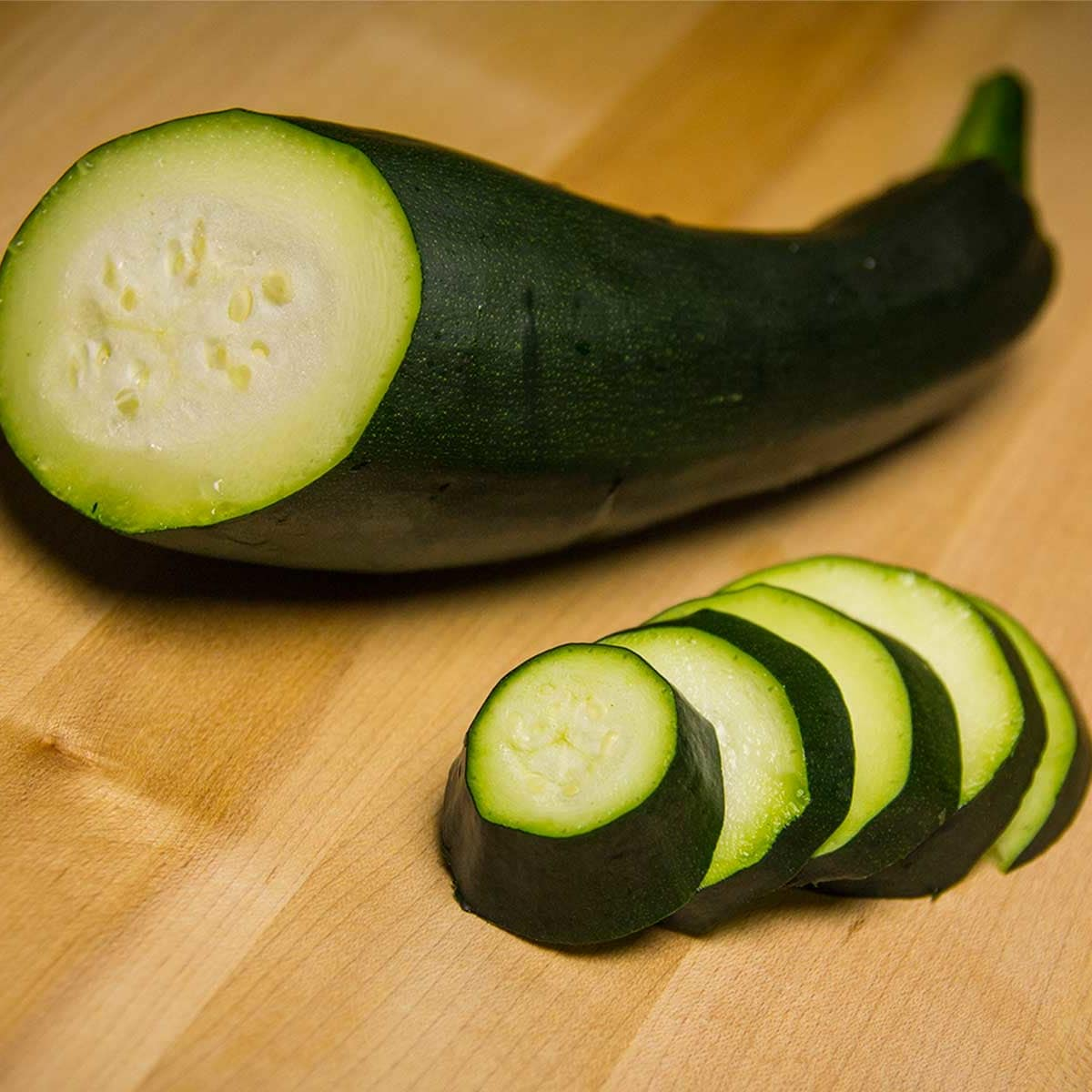 Photo of sliced seedless zucchini on wooden cutting board