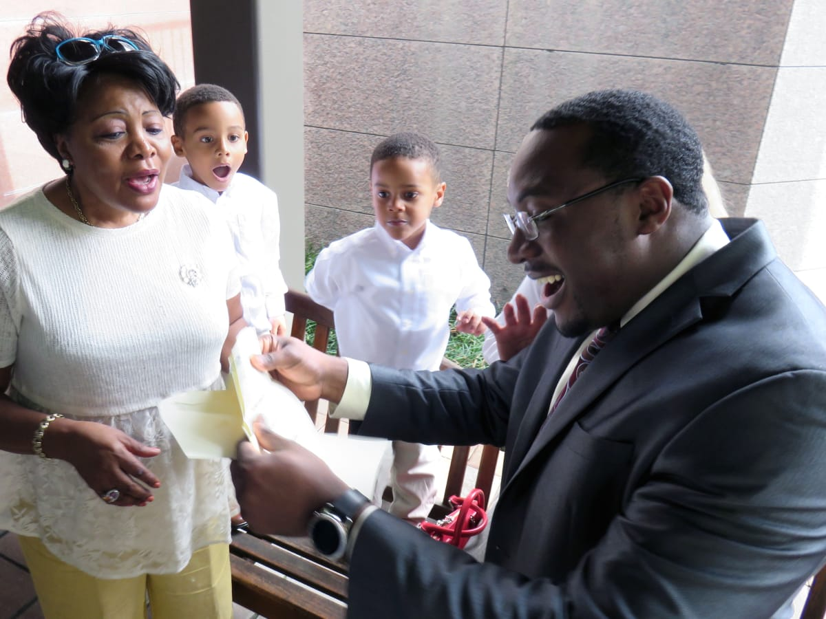 Eliel Arrey, his mother Magdalene and two of his three sons, Nolan at left and Antoine, react as Arrey discovers that he will be doing his residency at Houston Methodist
