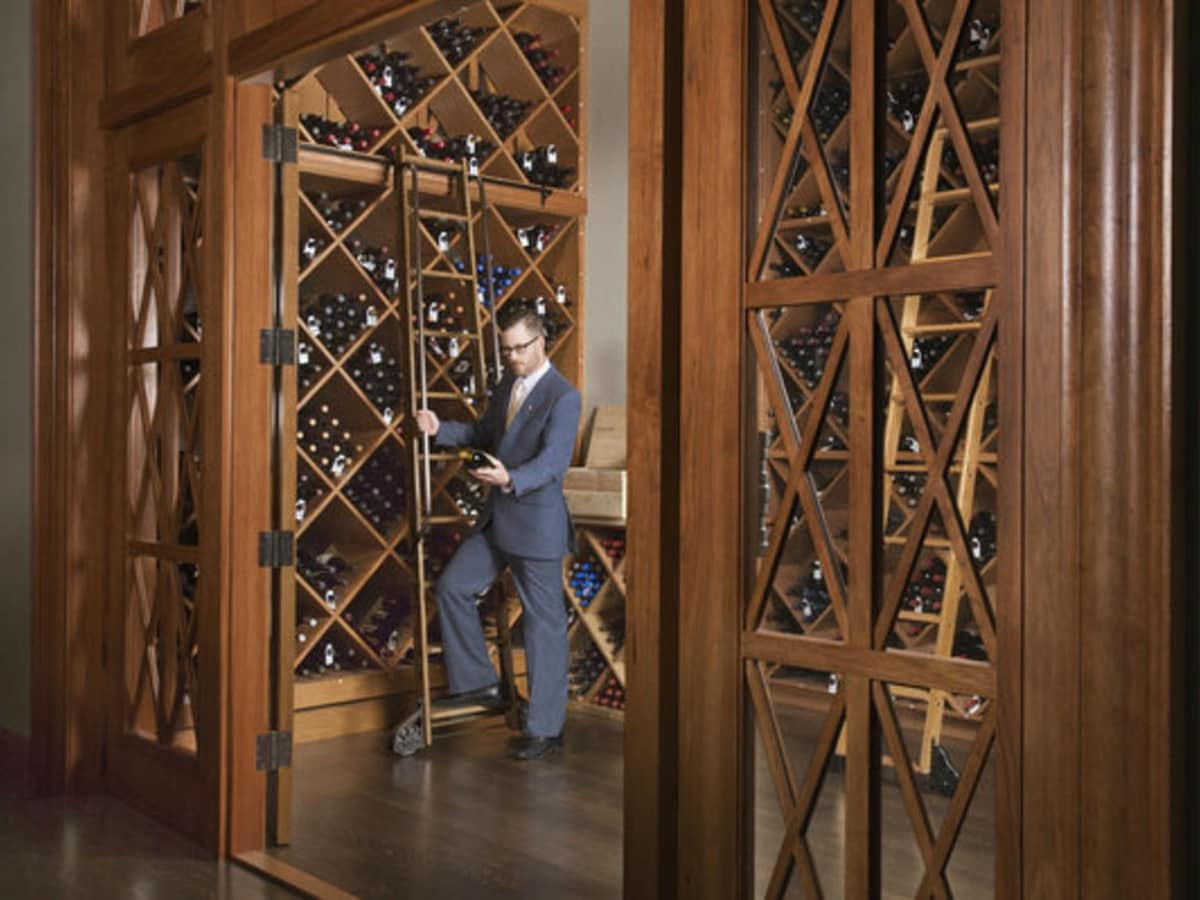 Man picking out bottles from a wine cellar