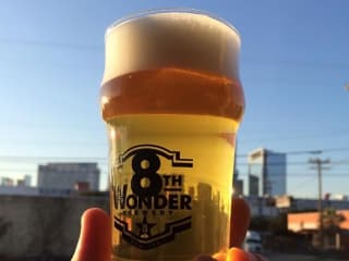 Eighth 8th Wonder Brewery glass of beer with skyline in background