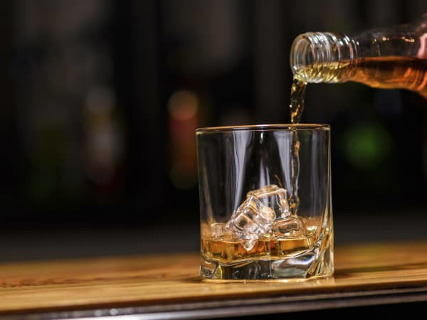 Whiskey being poured from a bottle into a glass