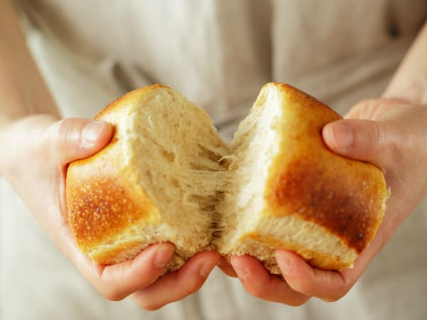 Person breaking apart bread