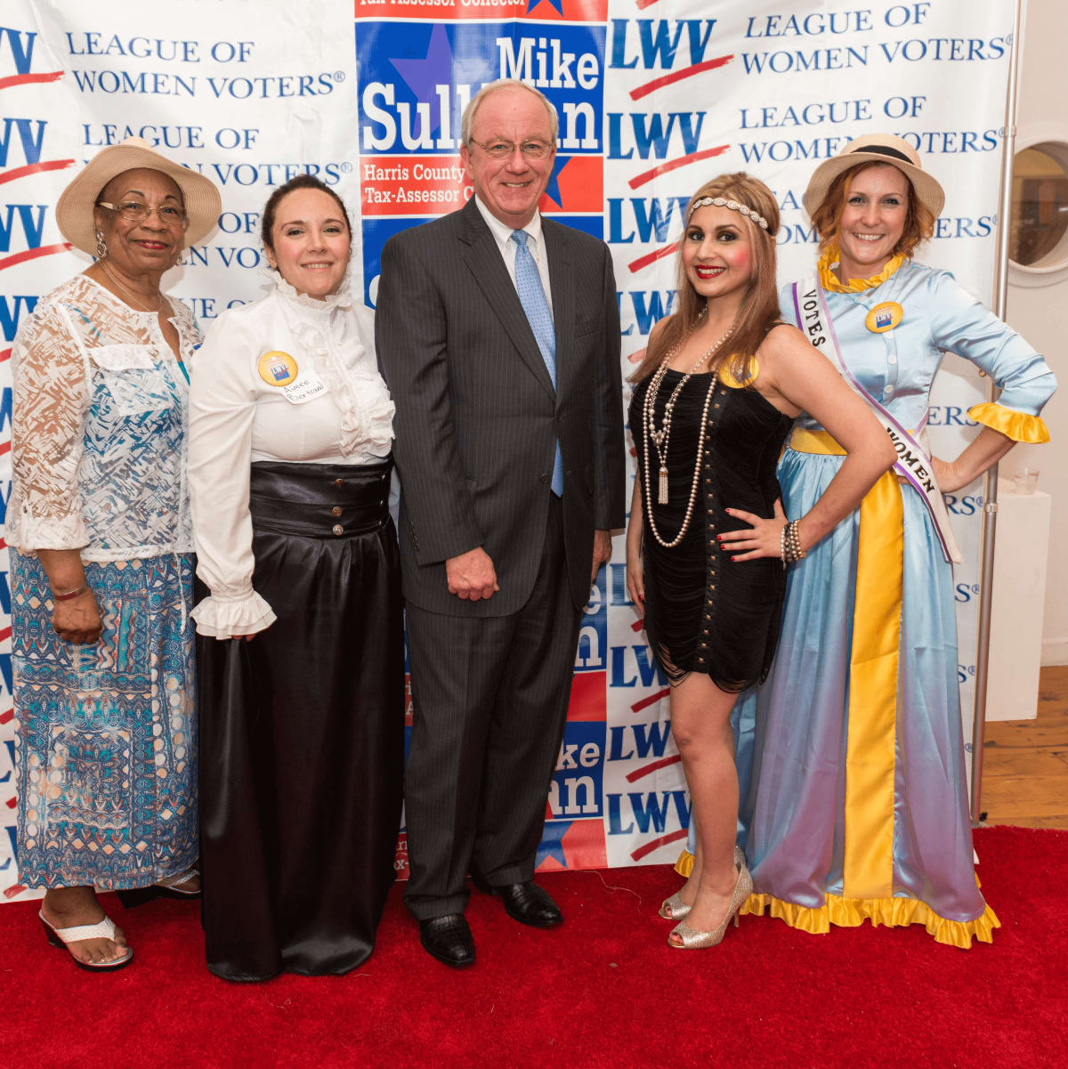 Houston's Women's Equality Day Celebration, Harris County Tax Assessor-Collector and Voter Registrar Mike Sullivan, flanked by Event Co Chairs Aimee Bertrand and Parisa Moayedi and event attendees