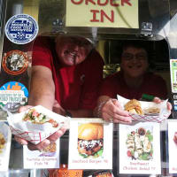 Houston Haute Wheels Food Truck Festival vendors holding out food