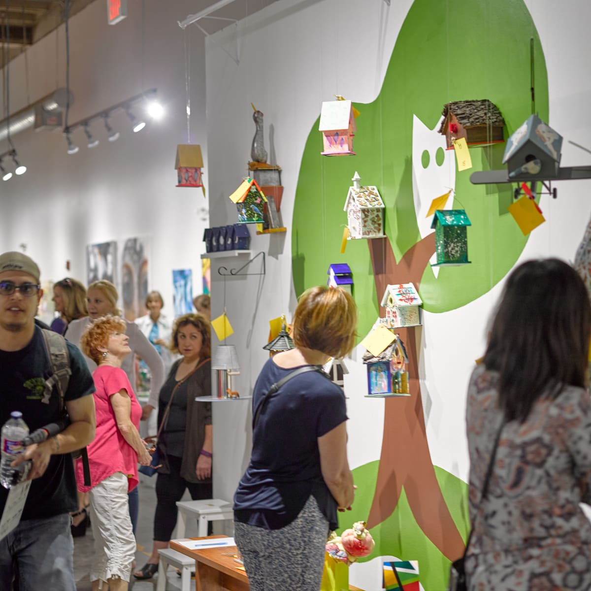 Guests perusing the artist birdhouses on display at Sawyer Yards Artist Stroll