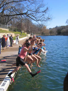 swimmers jumping into Barton Springs pool for Save Our Springs Polar Bear Splash