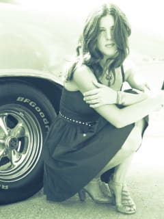 singer songwriter Amy Atchley in front of a car
