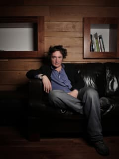 comedian and actor Dylan Moran sitting on a couch