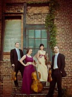 Members of the Jasper String Quartet standing in front of a building