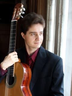 classical guitarist Alexander Milovanov holding a guitar