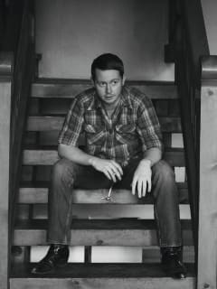 musician John Fullbright sitting on stairs