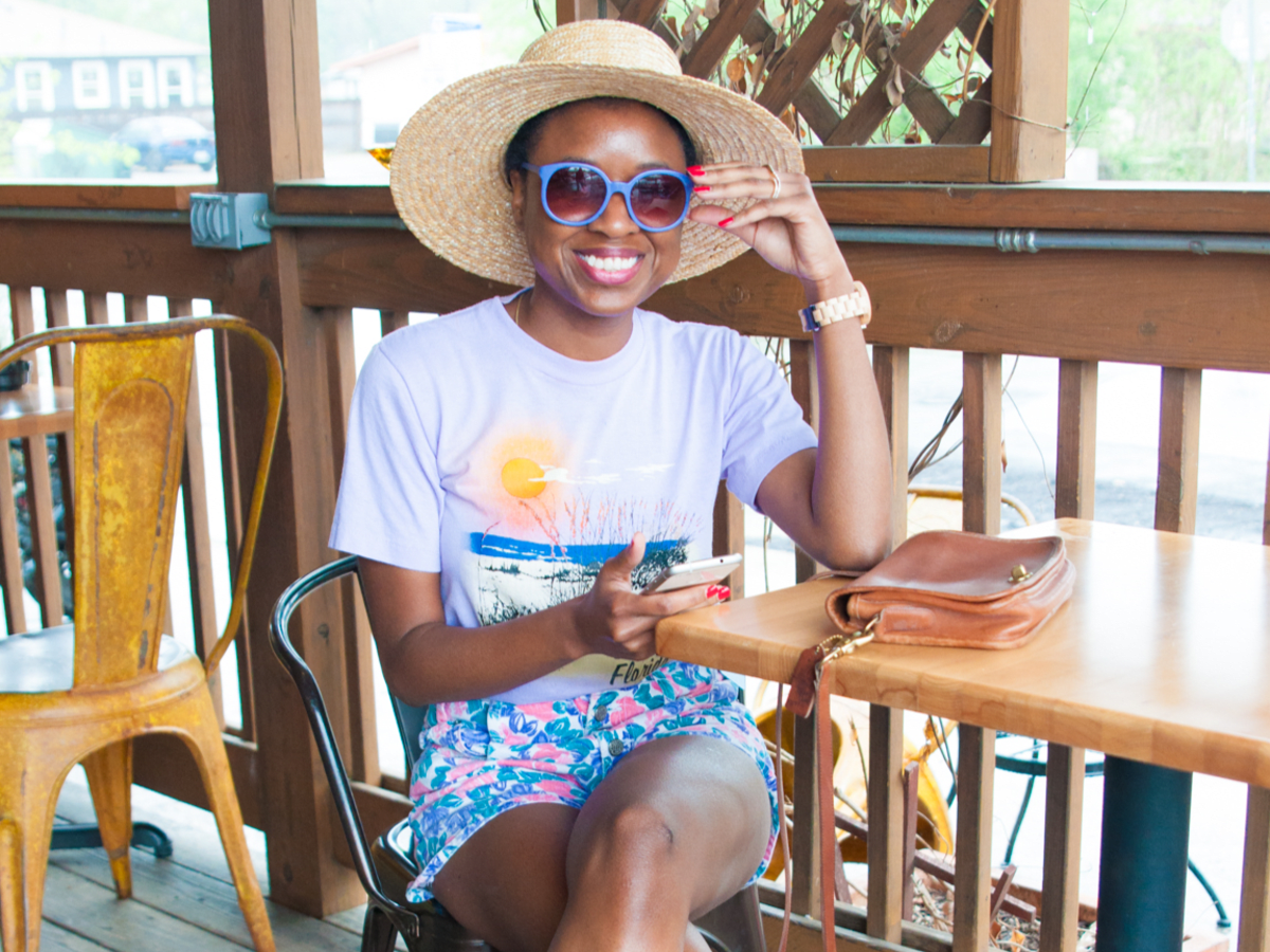 Sakeenah Aleem wears tourist t-shirt, colorful shorts, and wide brimmed straw hat in Austin, Texas