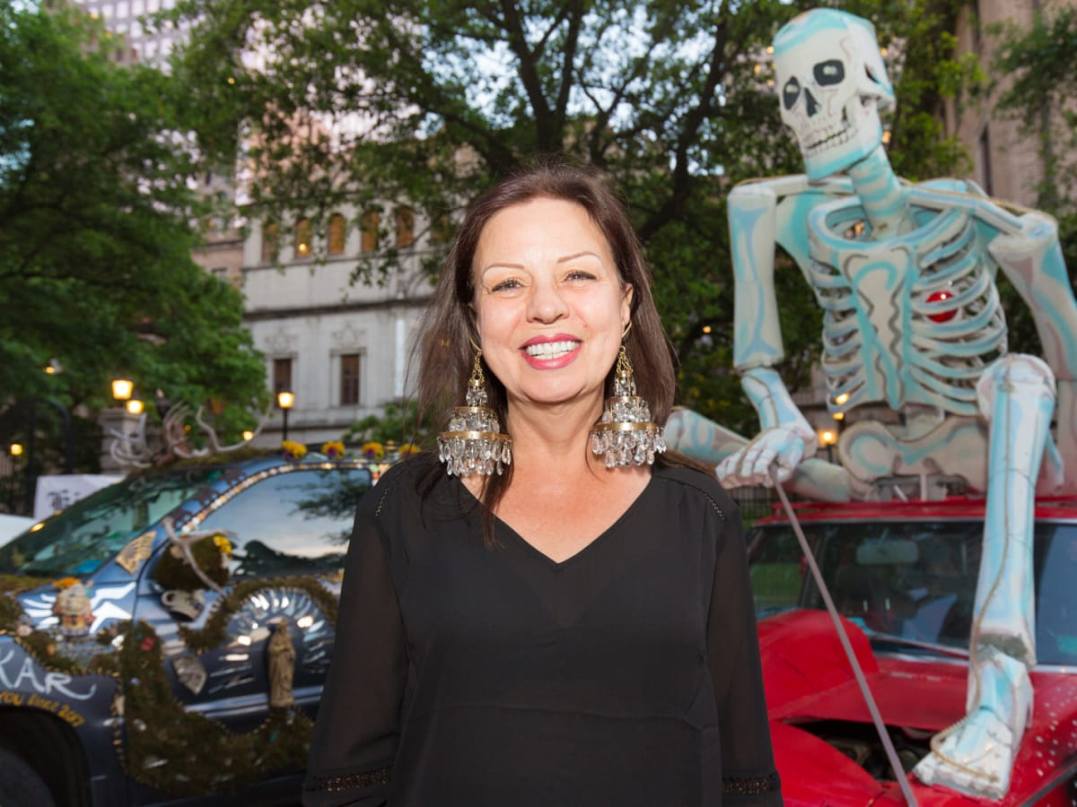 Audrey Crowson of Houston, wearing chandelier earrings, poses in from of a skeleton riding atop an Art Car at Legendary Art Car Ball