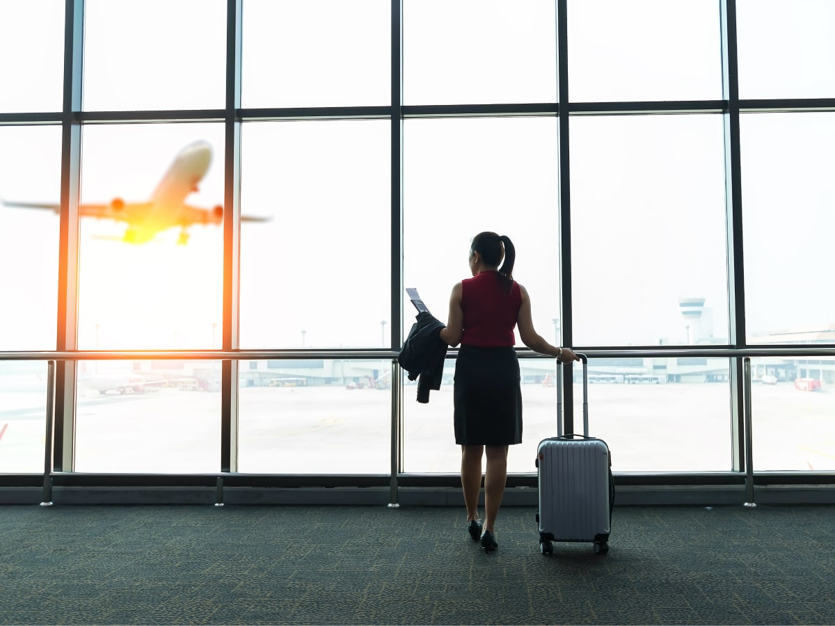 Woman at airport watching an airplane take off