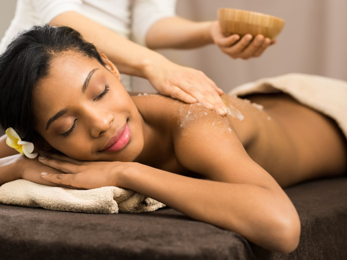Woman receiving a passion fruit agave body scrub
