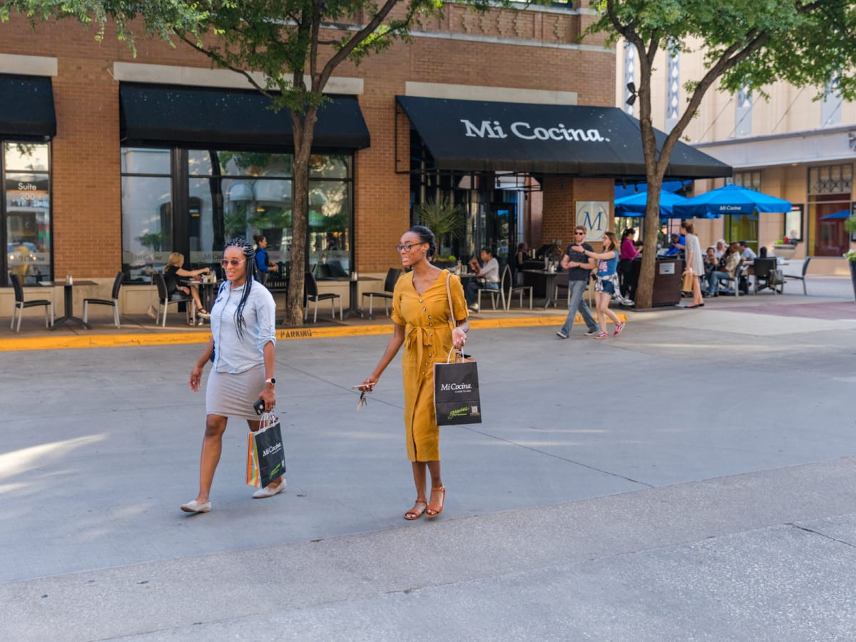 Two women walking in front of Mi Cocina