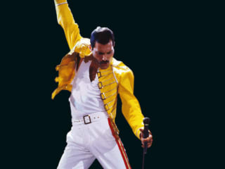 Freddie Mercury of Queen singing on stage with fist raised