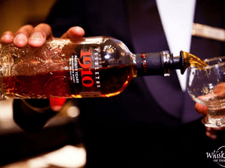bottle of whiskey being poured into glass at Whiskies of the World