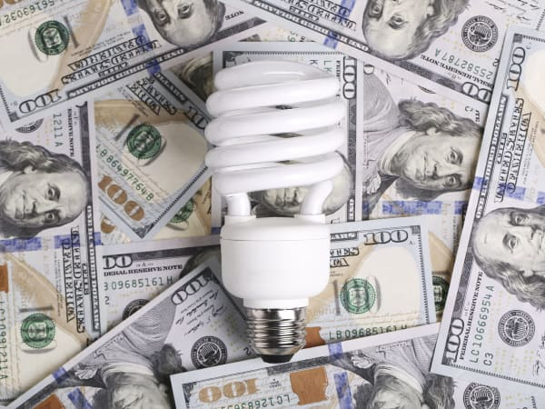 Compact fluorescent light bulb on a pile of cash