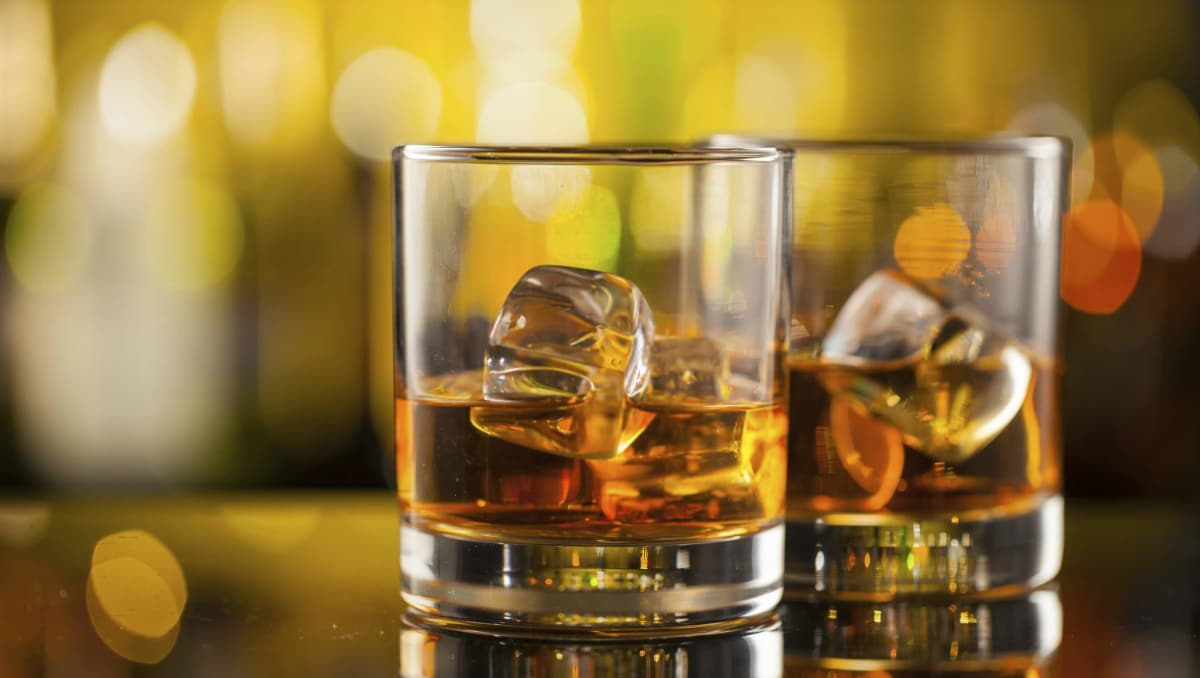 Two glasses of whiskey on a bar