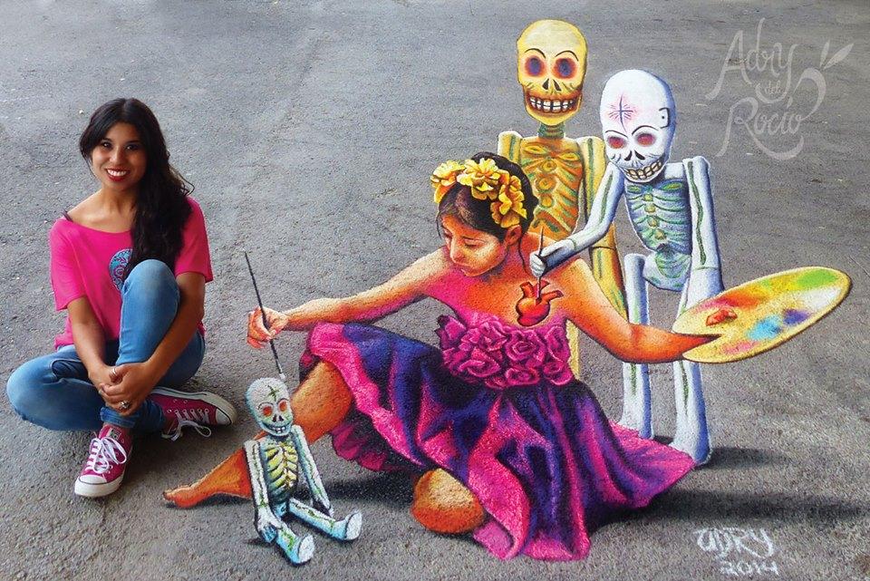 Adry del Rocío - Traditions - Obra en gis de calaveras dibujando a una niña que a su vez punta una calavera