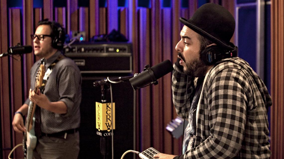Camilo Lara con sombrero bombín y camisa a cuadros enfrente de un micrófono en un estudio de grabación