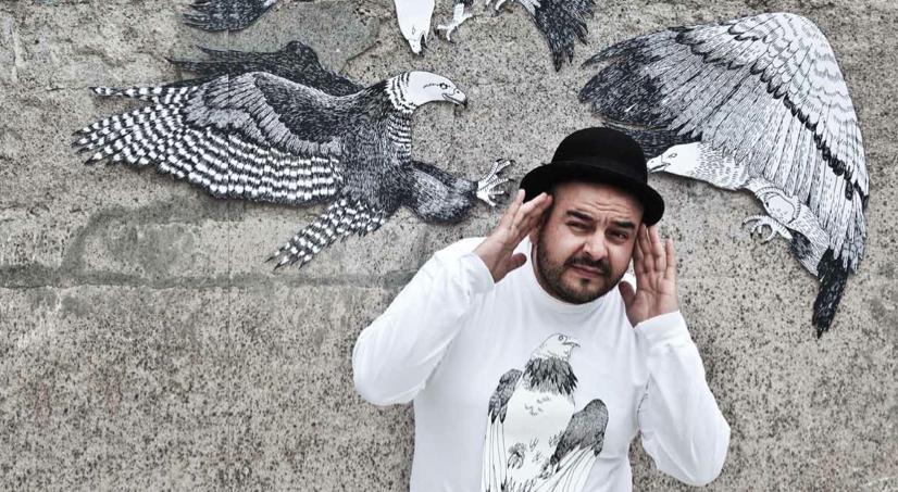 Camilo Lara con sombrero bombín playera blanca enfrente de una obra pintada en la pared en blanco y negro