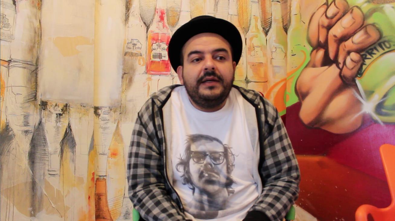 Camilo Lara con sombrero bombín playera blanca y camisa a cuadros enfrente de una pared gris con un paragüas negro