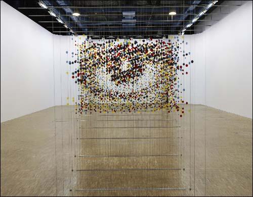 Damián Ortega - instalación de varios objetos circulares suspendidos por hilos transparentes formando un ojo