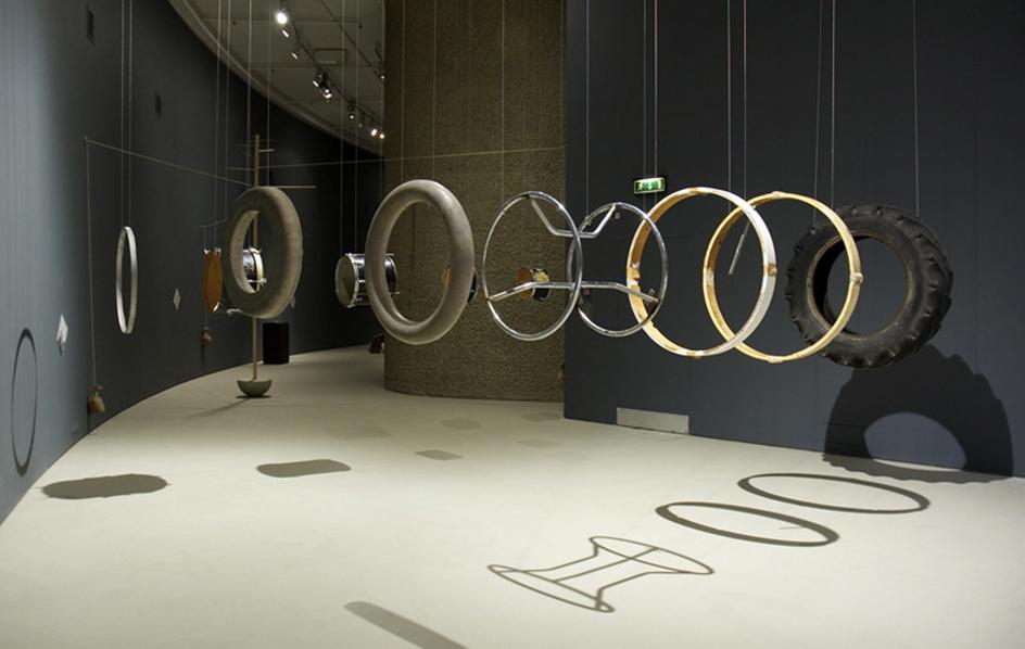 Damián Ortega - instalación de varios objetos circulares suspendidos por hilos transparentes