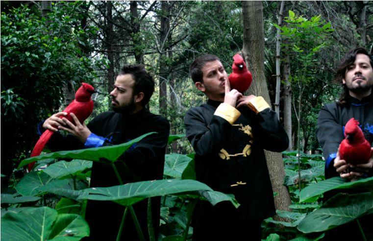 Liquits - fotografia con los tres miembros de la banda sosteniendo aves rojas en un parque público