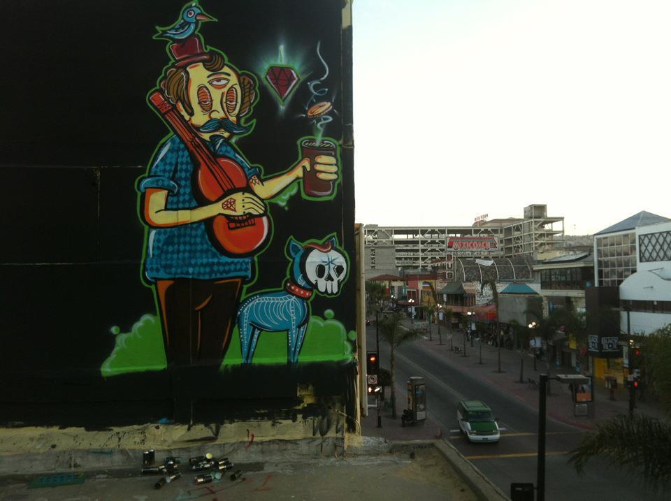 Ugo Villegas - Mural en graffiti de un señor sosteniendo una guitarra y un vaso en cada mano y un gato con una máscara en el rostro
