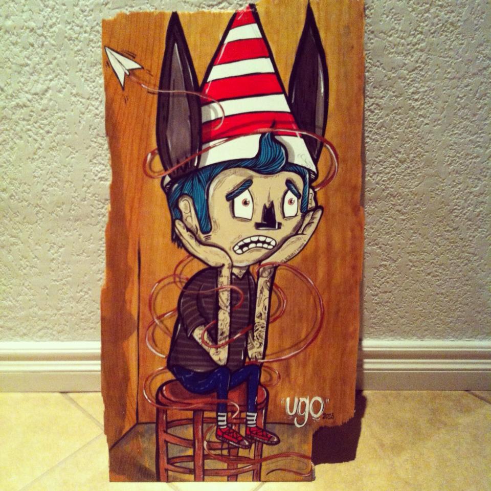 Ugo Villegas - pedazo de madera con la ilustración de un niño sentado un un banco con un cono como sombrero y orejas de burro