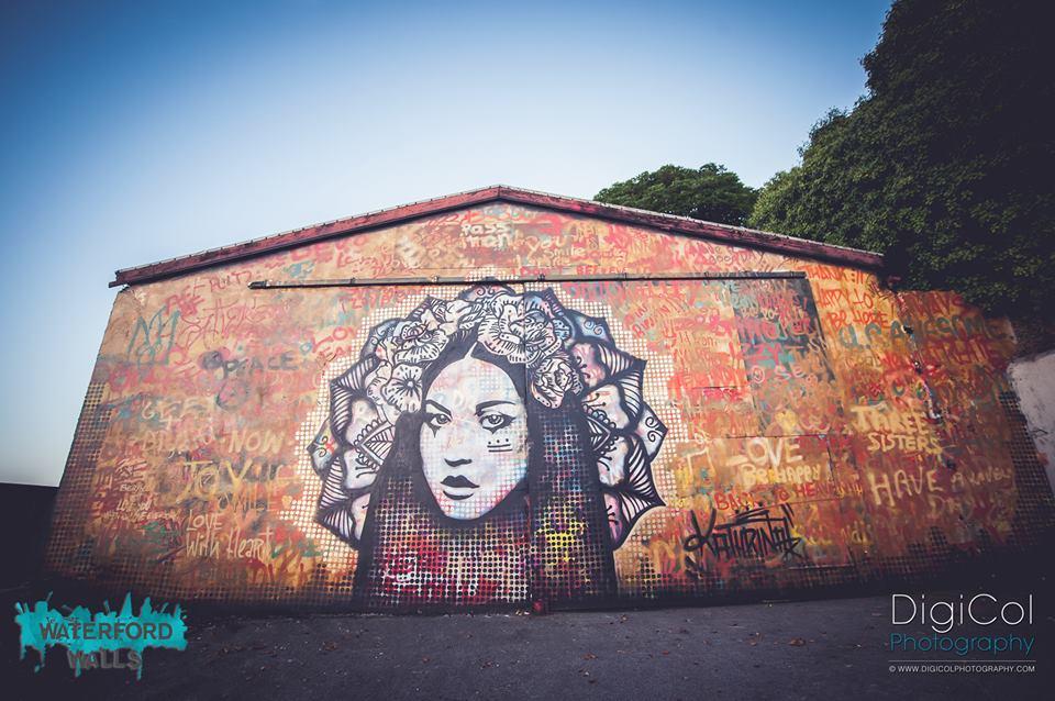 Kathrina Rupit - mural de rostro de mujer en blanco y negro adornada con flores en la cabeza