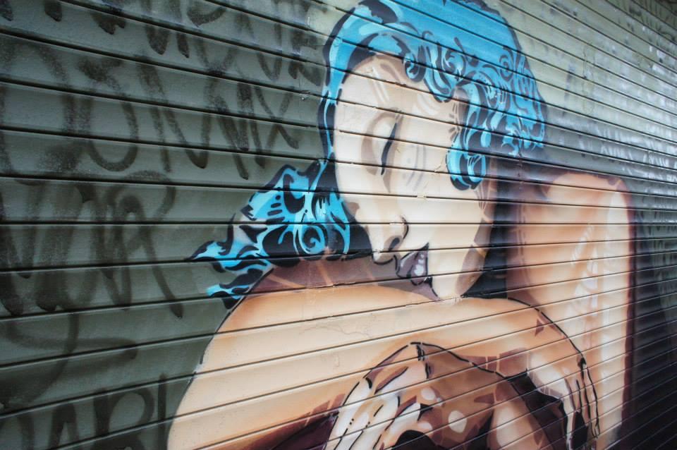 Kathrina Rupit -pintura sobre cortina de hierro con una mujer de cabello azul recostada sobre su rodilla
