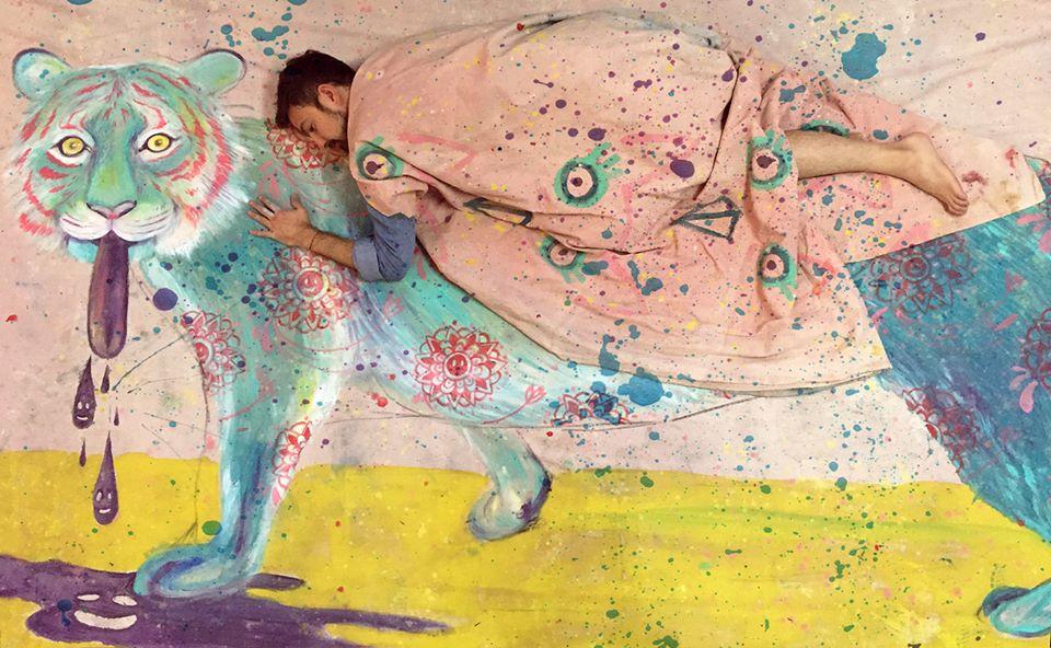Jorge Tellaeche - Jorge Tellaeche recostado sobre un lienzo que tiene un tigre