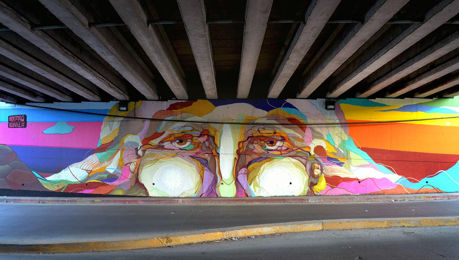Alonso Delgadillo - Vigilante - Mural debajo de un puente con un rostro y las manos cerca de los ojos.