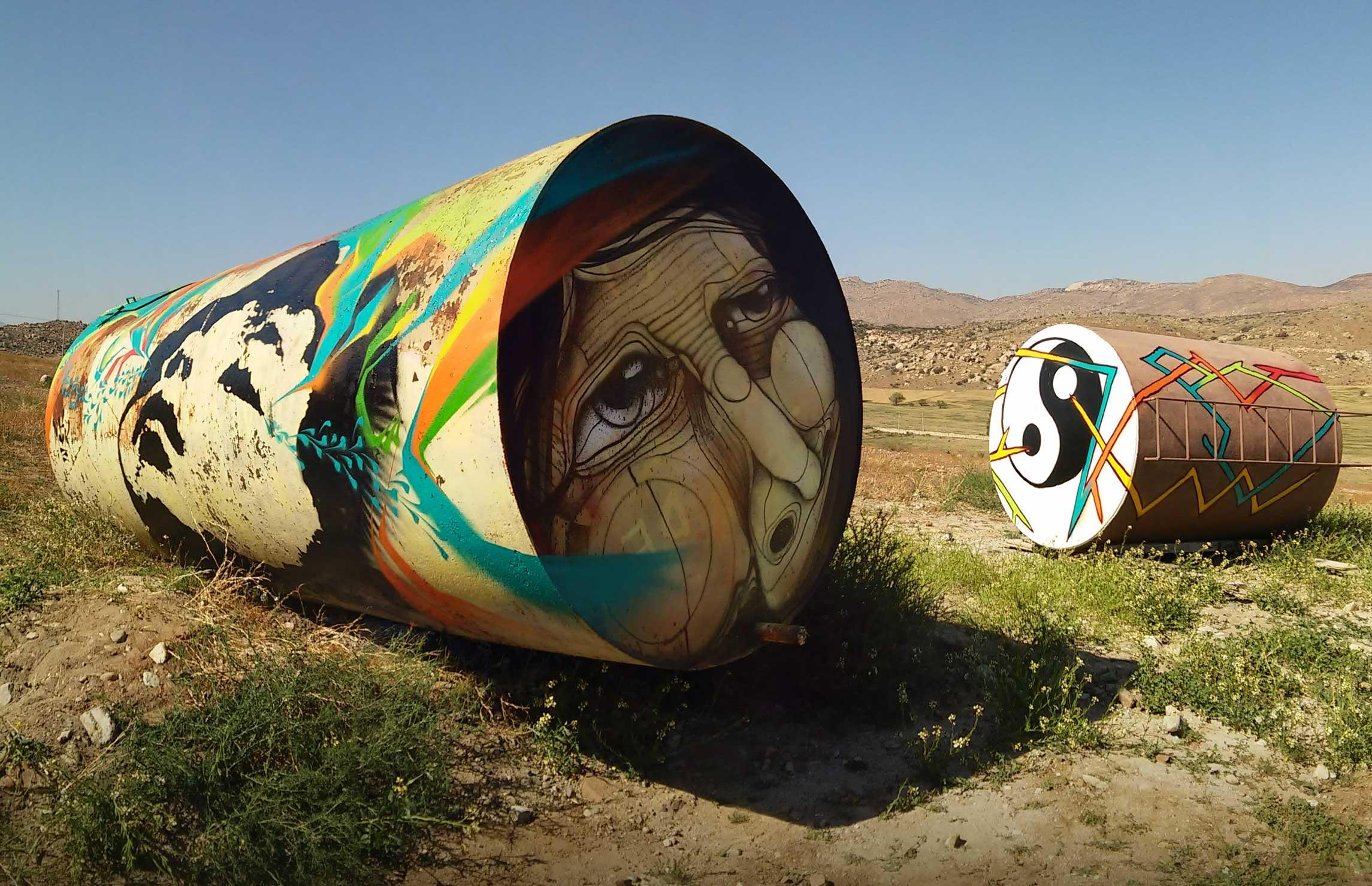 Alonso Delgadillo - Valle de las Palmas - Cilindros en un campo pintados con rostros y el símbolo yin yang