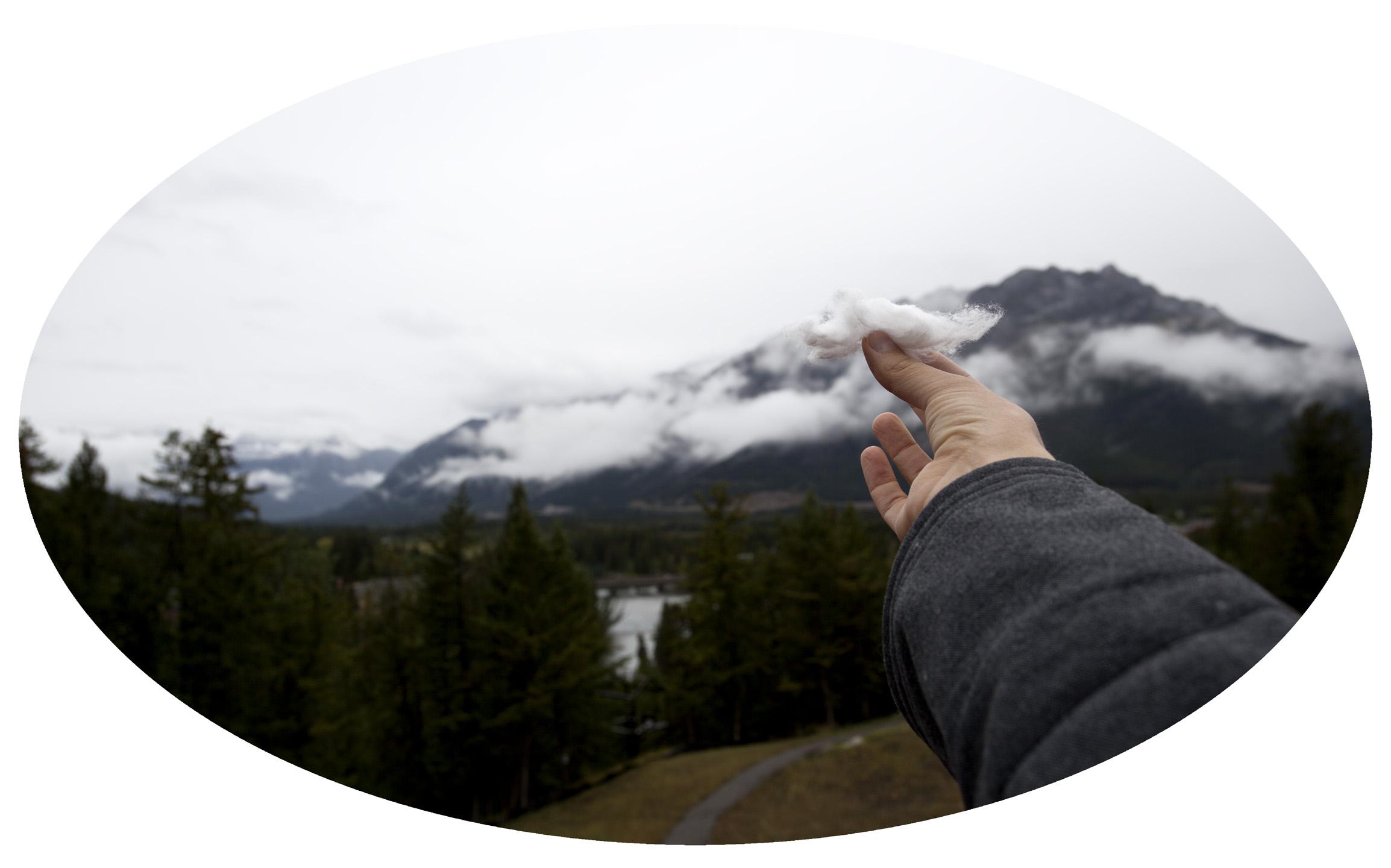 Daniela Edburg - fotografia de un una mano que sostiene un trozo de algodón en un paisaje con nubes