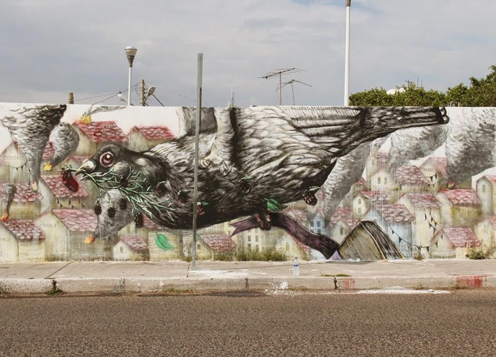 Ezequiel Frías Cheke - Mural de una paloma gigante que sobre vuela un poblado