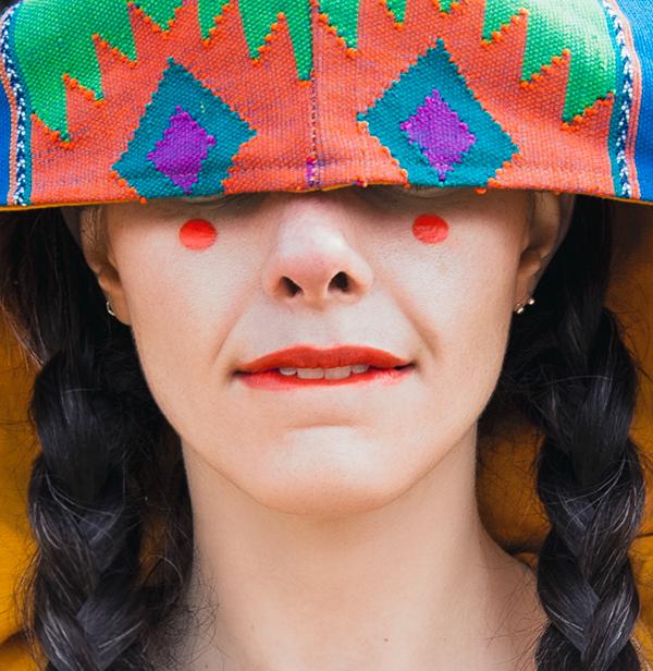 Marina Coracha - retrato de mujer con los ojos tapados por una manta con patrones en distintos colores llamativos