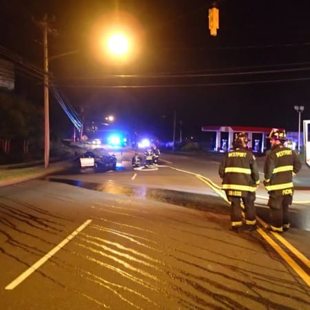 Westport firefighters respond to a crash scene after a car slammed into a pole and burst into flames on the Post Road early Saturday.