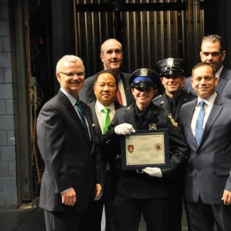 White Plains Police Officer Amy Carelli, center, received her Police Academy training certificate from Commissioner David E. Chong (left of her) and was joined on stage by several family members who also are serving or retired as police officers.