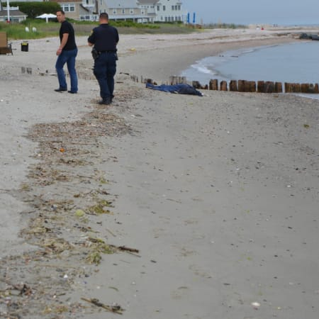 Fairfield police wait with the body of a man who washed up on shore Thursday afternoon.