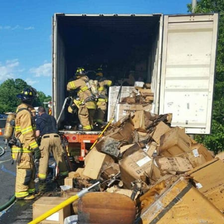 Firefighters empty the contents of a tractor-trailer after a fire Wednesday afternoon on I-95 in Stamford.