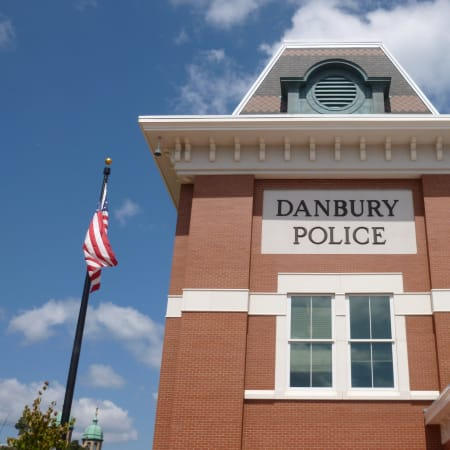 Police arrested a Danbury man after finding a stolen vehicle in front of his house Wednesday.
